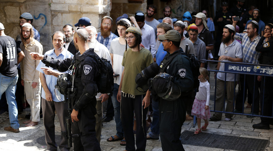 Israeli security forces stand guard as a group of Orthodox Jewish men leave after visiting the al-Aqsa mosque compound, commemorating the destruction of ancient Jerusalem temples some 2000 years ago, on August 14, 2016, in Jerusalem's Old City. © Ahmad Gharabli