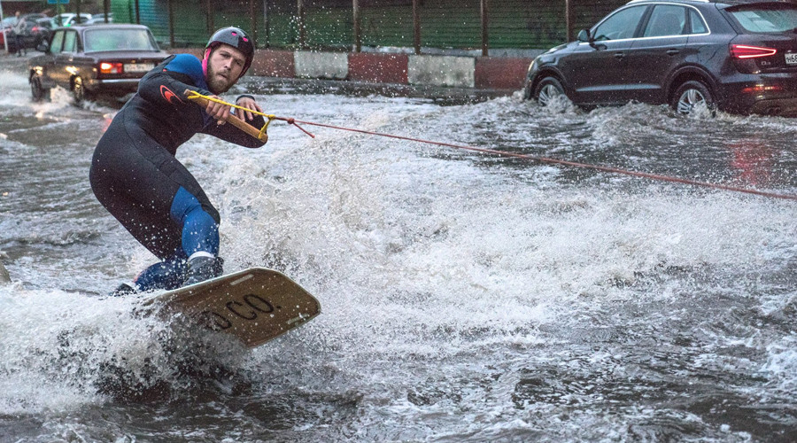 Watch man surf giant puddle on Moscow's rainiest day ever (VIDEO)
