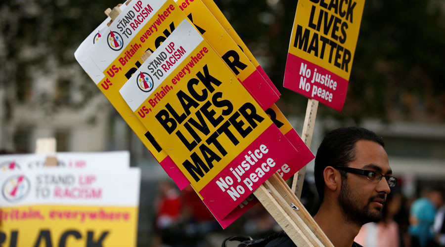 "A supporter of the UK branch of ""Black Lives Matter"" hands out placards at the start of a demonstration in London, Britain August 5, 2016.  © Peter Nicholls"