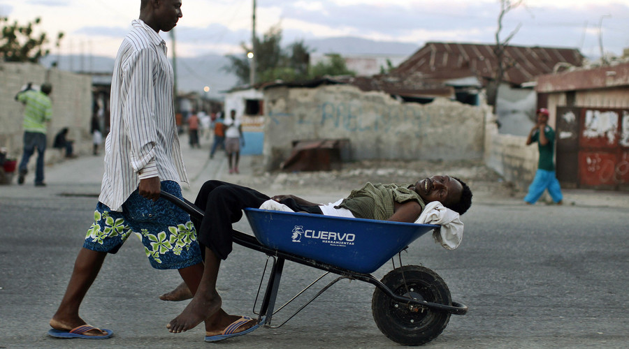 A Haitian with symptoms of cholera is transported in a wheelbarrow in the slums of Cite-Soleil in Port-au-Prince November 19, 2010. © Eduardo Munoz