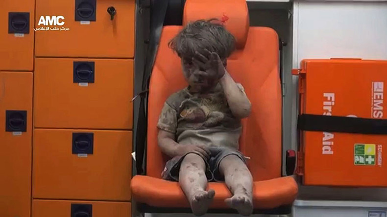 Omran, a four-year-old Syrian boy covered in dust and blood, in an ambulance after being rescued from the rubble of a building hit by an air strike in the rebel-held Qaterji neighbourhood of the northern Syrian city of Aleppo.© AMC