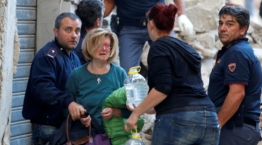 A woman (2nd L) cries after been rescued from her home following a quake in Amatrice, central Italy, August 24, 2016. © Remo Casilli