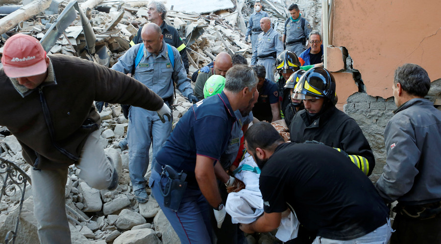 Rescuers carry a person on a stretcher following a quake in Amatrice, central Italy, August 24, 2016. © Remo Casilli
