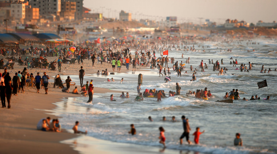Tourists dip in the Mediterranean Sea to cool off on a hot day in Gaza City. © Suhaib Salem