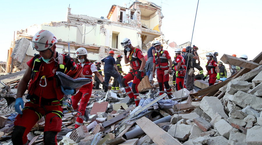 Rescuers walk through rubble following the earthquake in Amatrice, central Italy, August 24, 2016. © Stefano Rellandini