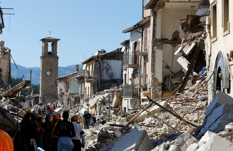 People stand next collapsed buildings following an earthquake in Amatrice, central Italy, August 24, 2016. © Stefano Rellandini