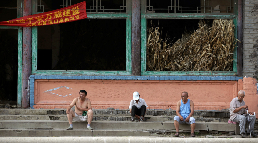 Villagers sit on stairs outside an abandoned old theatre building in an area where land is sinking near a coal mine in Kouquan township of Datong, China's Shanxi province, August 1, 2016. © Jason Lee
