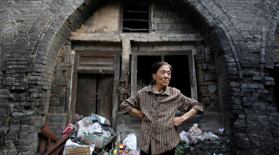 Li Yonghua, 65, stands in front of her damaged cave house in an area where land is sinking next to a coal mine, in Helin village of Xiaoyi, China's Shanxi province, August 2, 2016. © Jason Lee