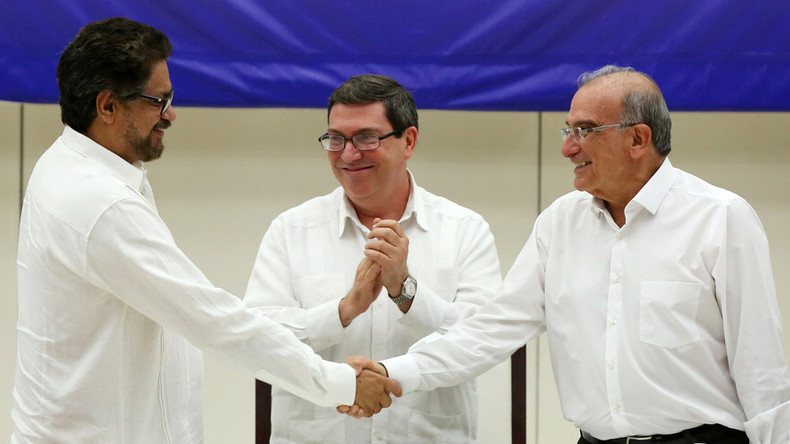 FARC's Ivan Marquez (L) and Colombia's Humberto de la Calle (R) shake hands over their historic peace deal Wednesday while Cuba's Foreign Minister Bruno Rodriguez looks on. © Alexandre Meneghini