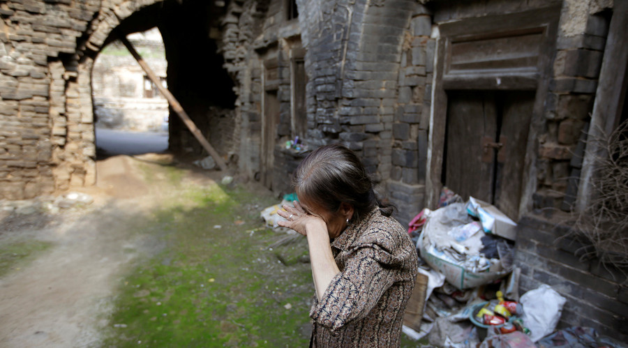 Li Yonghua, 65, wipes her eyes in front of her damaged cave house in an area where land is sinking next to a coal mine, in Helin village of Xiaoyi, China's Shanxi province, August 2, 2016. © Jason Lee