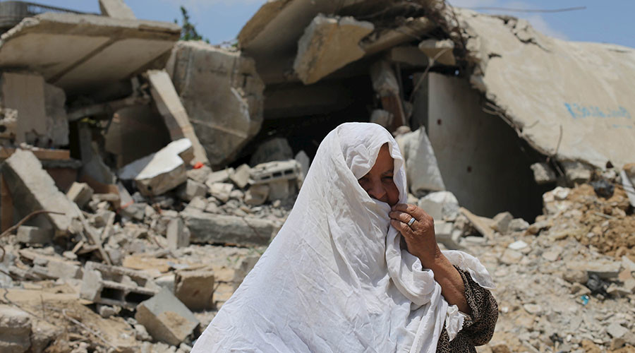 A Palestinian woman looks on as she stands in front of the ruins of her house, that witnesses said was destroyed by Israeli shelling during a 50-day war last summer, in Khan Younis in the southern Gaza Strip. © Ibraheem Abu Mustafa