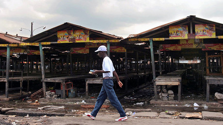 A man walks past empty market stalls in Republic of Congo's capital of Brazzaville. ©Jiro Ose