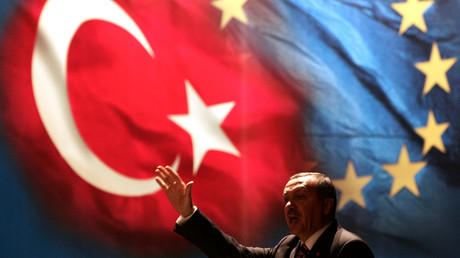 Turkish Prime Minister Tayyip Erdogan gestures under Turkish and EU flags in Istanbul, October 12, 2005. © Fatih Saribas