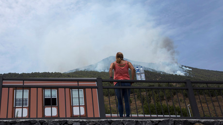 A resident watches the smoke from a fire in Las Manchas on the Canary Island of La Palma in Spain, August 6, 2016. © Borja Suarez