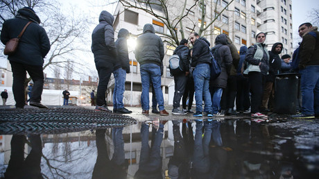 Migrants are reflected in a puddle as they queue in front of the compound of the Berlin Office of Health and Social Affairs (LAGESO) © Fabrizio Bensch