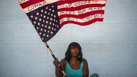 Chocolate, 36, an activist who wants to be identified by only her nickname, waves an American flag upside down while posing for a portrait in Ferguson, Missouri July 24, 2015. © Adrees Latif