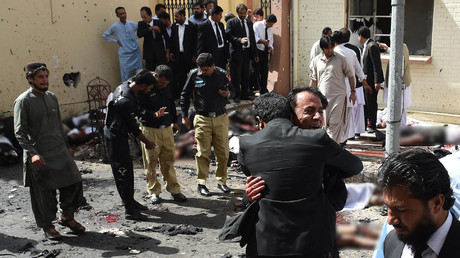 Pakistani lawyers react as they stand near the bodies of victims of a bomb explosion at a government hospital premises in Quetta on August 8, 2016. © Banaras Khan