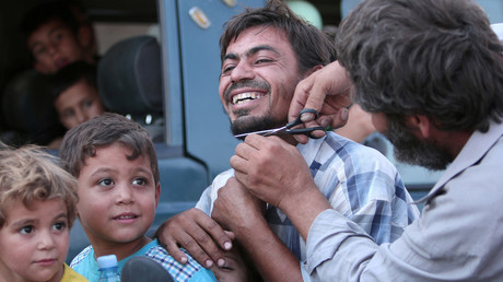 A man cuts the beard of a civilian who was evacuated with others by the Syria Democratic Forces (SDF) fighters from an Islamic State-controlled neighbourhood of Manbij, in Aleppo Governorate, Syria, August 12, 2016. © Rodi Said