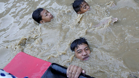A resident holds onto a rescue boat as others wade along a flooded street, brought by monsoon rains in San Mateo, Rizal, Philippines, August 13, 2016. © Erik De Castro