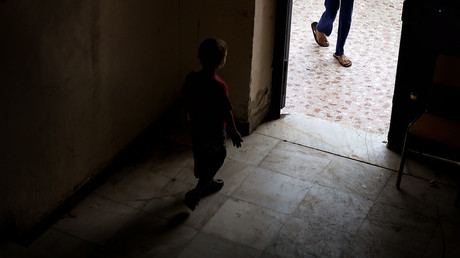 A boy is seen in abandoned school used by volunteers for hosting families of refugeees from Syria and Afghanistan in Athens. © Aris Messinis