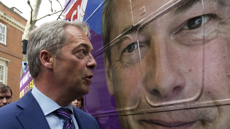 Leader of the United Kingdom Independence Party (UKIP), Nigel Farage gazes at a large-scale image of his face on the side of the bus. © 