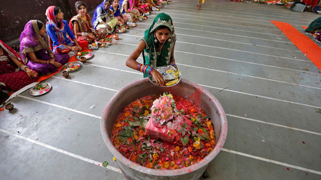 A girl places offerings on Shivling (a symbol of Lord Shiva) on the last day of Jaya Parvati Vrat festival at a temple in Ahmedabad, India, July 21, 2016. © Amit Dave