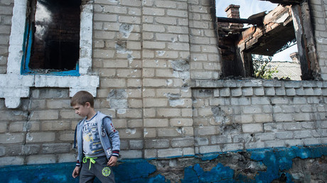 A child walks by a house damaged during a mortar shelling in the village of Oleksandrivka, Donetsk Region.© Iliya Pitalev