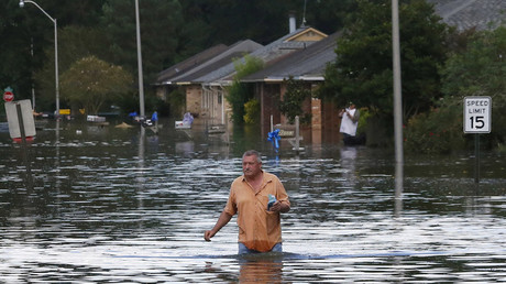 A man wades through a flooded street in Ascension Parish, Louisiana, U.S., August 15, 2016. © Jonathan Bachman