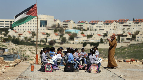 A teacher gives a class to Palestinian bedouin students outdoors near the Jewish settlement of Maale Adumim, in the West Bank village of Al-Eizariya, east of Jerusalem © Ammar Awad