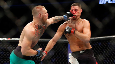 Conor McGregor (L) hits Nate Diaz with a left during UFC 202 © Steve Marcus / Getty Images / AFP