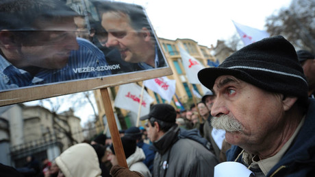A participant of a rally holds a banner with a photo of Hungarian Prime Minister Viktor Orban (R) and Zsolt Bayer (L) during a demonstration, against racism, segregation, and hate speech in connection with a recent, anti-Roma article, on January 13, 2013 in Budapest. © Attila Kisbenedek