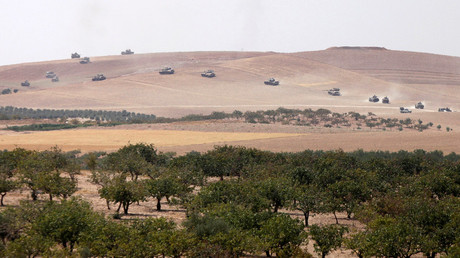 Turkish army tanks and Turkish-backed Syrian fighters make their way in the Syrian border town of Jarablus as it is pictured from the Turkish town of Karkamis, in the southeastern Gaziantep province, Turkey, August 24, 2016. © Stringer