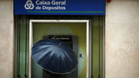 A man uses an ATM machine at a Caixa Geral Depositos branch in downtown Lisbon, Portugal. © Rafael Marchante