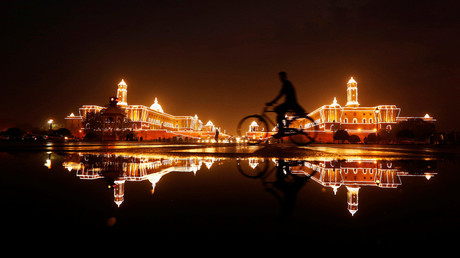 A cyclist rides past the Illuminated Indian Defence Ministry (L), Presidential Palace (C) and Home Ministry ahead of India's Independence Day celebrations in New Delhi © Adnan Abidi