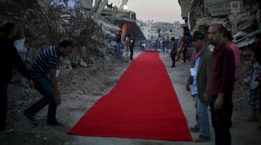 FILE PHOTO: Palestinians place a red carpet between the ruins of houses, that witnesses said were destroyed by Israeli shelling during a 50-day war last summer, before they display a film on the war in the east of Gaza City May 12, 2015. © Mohammed Salem