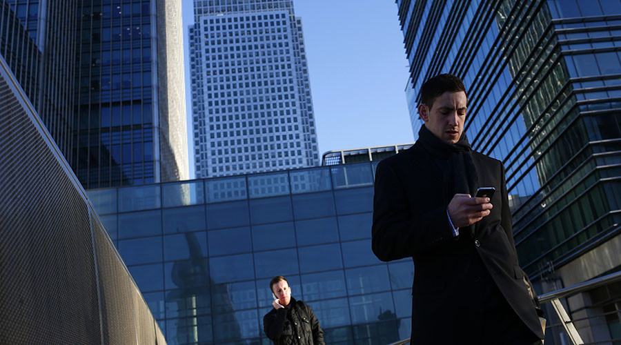 A worker looks at his phone at the Canary Wharf business district in London. ©Eddie Keogh