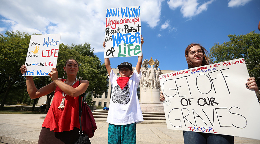 Protesters hold signs outside the U.S. District Court in Washington, where a hearing was being held to decide whether to halt construction of an oil pipeline in parts of North Dakota where a Native American tribe says it has ancient burial and prayer sites, September 6, 2016. © Kevin Lamarque
