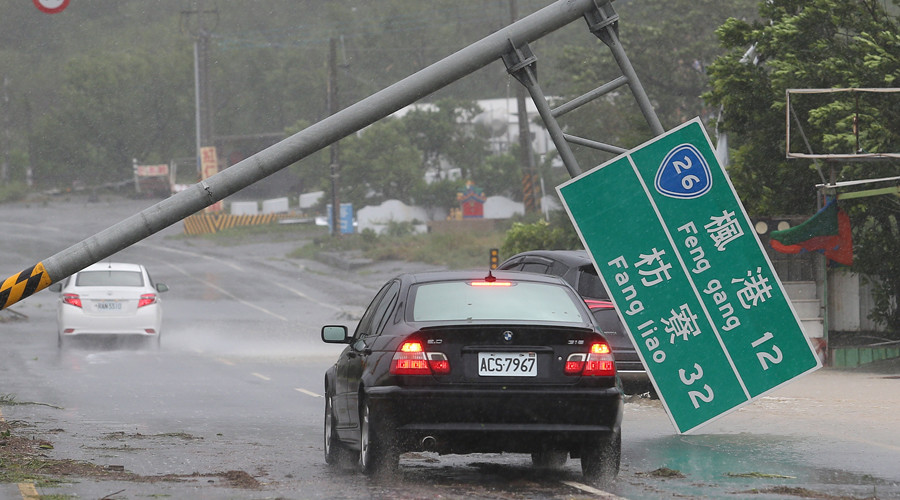 A car runs past a collapsed traffic sign, toppled by strong winds of typhoon Meranti, in Kaohsiung © Stringer