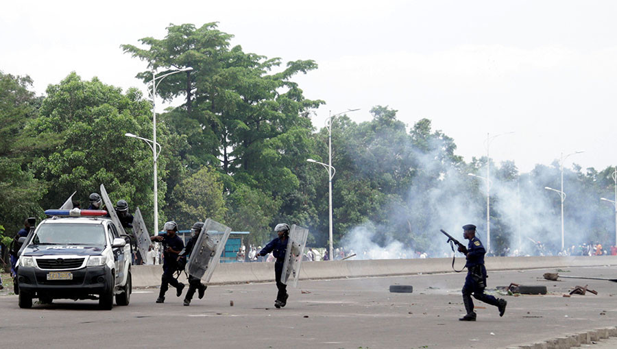 Congolese policemen run to their vehicle during a clash with opposition activists participating in a march to press President Joseph Kabila to step down in the Democratic Republic of Congo's capital Kinshasa, September 19, 2016. ©Kenny Katombe