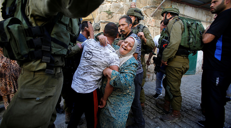 A Palestinian woman cries as she holds her relative before he was detained by Israeli soldiers during a searching raid by Israeli troops in the West Bank city of Hebron September 20, 2016 © Mussa Qawasma