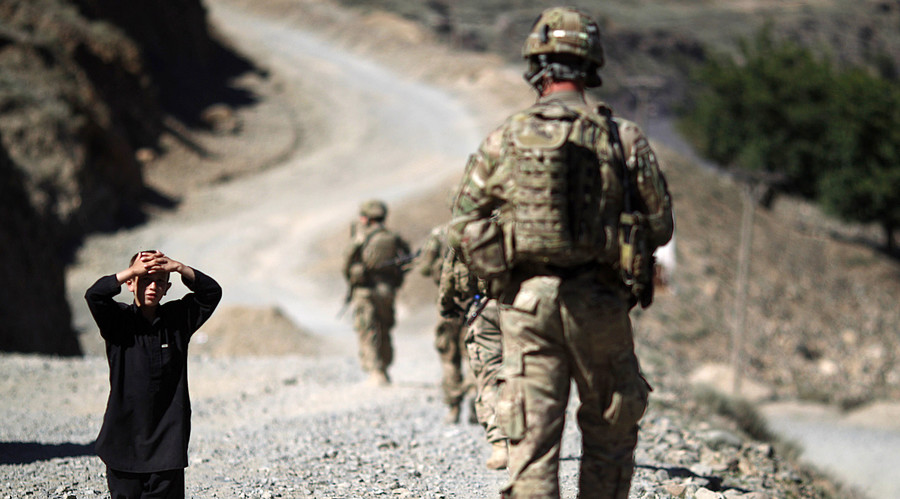 A boy watches soldiers from the U.S. Army's Charlie Company during a patrol near Dokalam village in Kunar Province. File photo. © Tim Wimborne