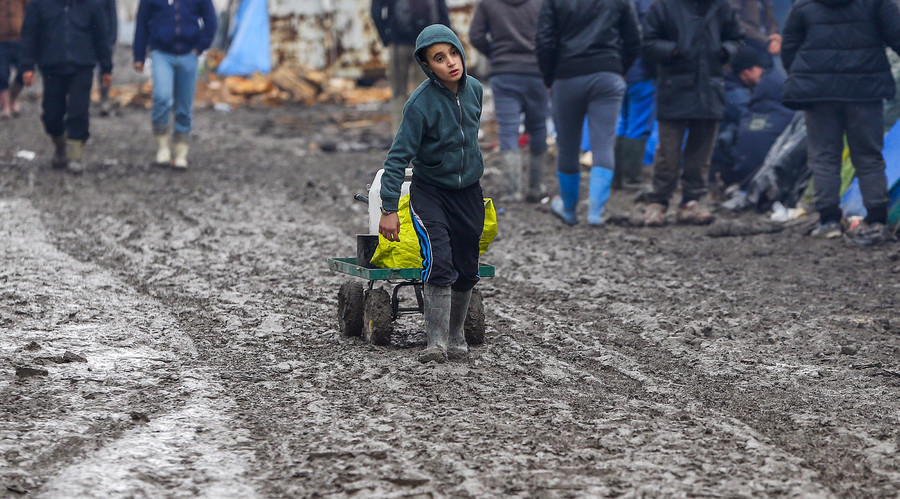 A young migrant pulls a trolley in a muddy field at a camp of makeshift shelters for migrants and asylum-seekers from Iraq, Kurdistan, Iran and Syria, called the Grande Synthe jungle, near Calais, France. © Yves Herman