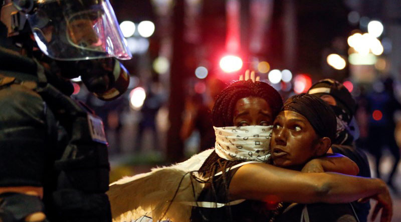 Two women embrace while looking at a police officer in uptown Charlotte, NC during a protest of the police shooting of Keith Scott, in Charlotte, North Carolina, U.S. September 21, 2016. © Jason Miczek