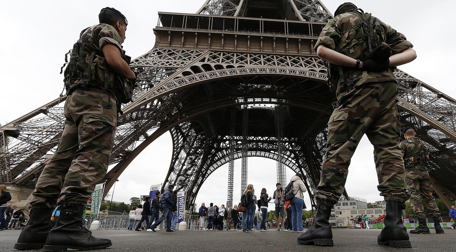 Soldiers stand by tourists as they patrol near the Eiffel Tower in Paris. © Gonzalo Fuentes