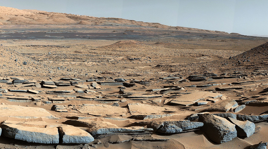 """A view from the """"Kimberley"""" formation on Mars taken by NASA's Curiosity rover. The strata in the foreground dip towards the base of Mount Sharp, indicating flow of water toward a basin  that existed before the larger bulk of the mountain formed. © NASA"""
