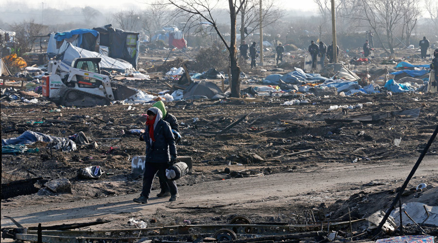 """Migrants walk in the dismantled area of the camp for migrants called the """"Jungle"""", in Calais, France, March 14, 2016. © Pascal Rossignol"""