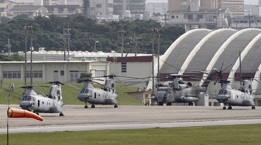 Four Sea Knight transport helicopters and a Super Stallion helicopter are parked at Marine Corps Air Station Futenma in Ginowan on Okinawa. © Toru Hanai