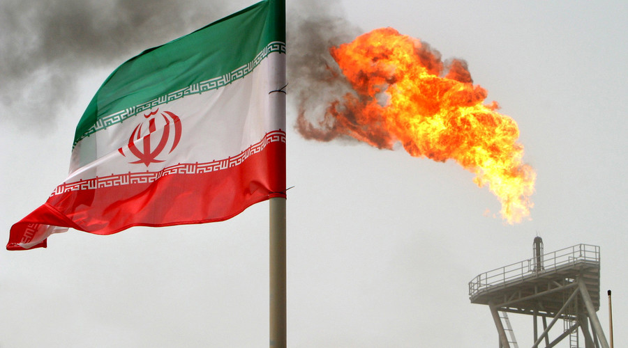 A gas flare on an oil production platform in the Soroush oil fields is seen alongside an Iranian flag © Raheb Homavandi
