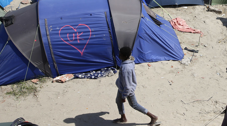 A heart and UK symbol are marked on the side of a tent as a migrant walks in the make-shift camp, called the jungle, in Calais, France © Pascal Rossignol