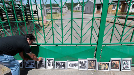 A participant of the European Meeting of Antiracist Leaders places a picture in front of a pig farm, situated at the site of a former Roma concentration camp, to commemorate victims of the Holocaust during World War Two in the village of Lety © David W Cerny